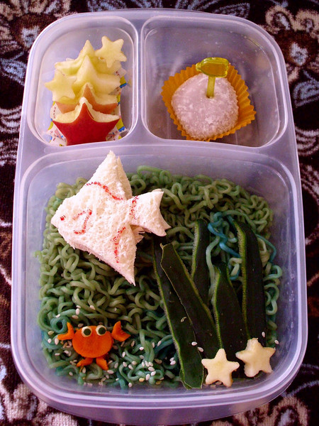 Little angel fish tuna sandwich is swimming in colored Top Ramen with a carrot crab and apple starfish. Smaller compartments are filled with apple starfish and a Taro Mochi. Photo credit: A Pocket Full of Buttons  http://bit.ly/98glde