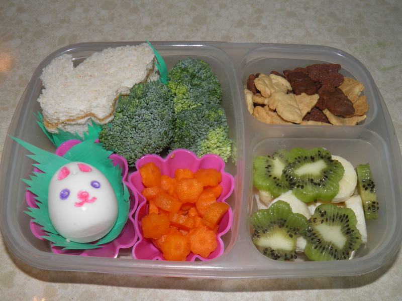 "Lunch today:  Hazelnut butter bunny sandwiches, bunny shaped hard boiled egg (decorated with food safe pens), broccoli trees, carrot flowers, banana and kiwi flowers and graham cracker and chocolate bunny wafers.  ""Hop on over and take a nibble or two"" thanks to Two Little Lunches"