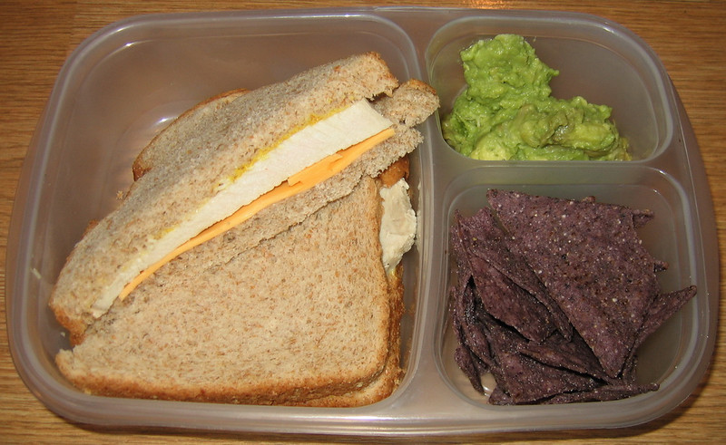 Homemade guacamole with blue corn chips and a sandwich. Add a shiny pippin apple and you're all set!