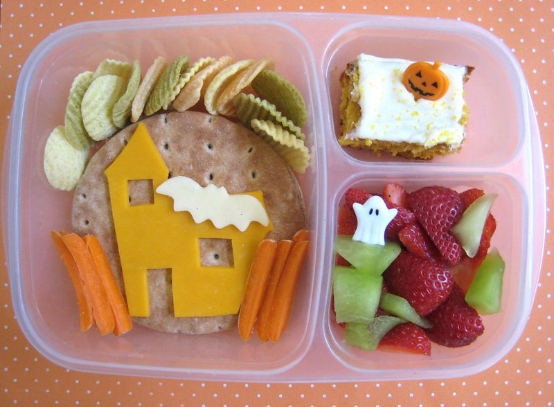 Spooky Haunted House Bento! Cream cheese & jelly sandwich, made with Santa Cruz Organic Blackberry-Pomegranate Jam and Nature's Own Whole Wheat Sandwich Rounds. The bread is such a nice blank canvas that I just had to decorate it. We have an orange cheddar haunted house (I cut the extra doors and windows as best I could), with a spooky white cheddar bat flying by, and some rickety carrot fencing. Up top are veggie chips, they don't fit in the theme, but I needed to put something there. Maybe they are storm clouds? To the right, he has a piece of pumpkin cake with a jack-o-lantern pick and strawberries/honeydew with a spooky little ghost. Picks are from the Dollar Tree in the Halloweeh section. Courtesy of What's For Lunch at Our House  http://bit.ly/9N8vgL