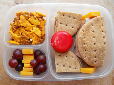 On Nature's Own Whole Wheat Rounds - a turkey and cheese sandwich and PB&J. Also in the large compartment is a Babybel.  Some cheddar cheese chunks and red seedless grapes, Annie's cheddar bunny snack mix. Lots more here: http://easybentos.blogspot.com