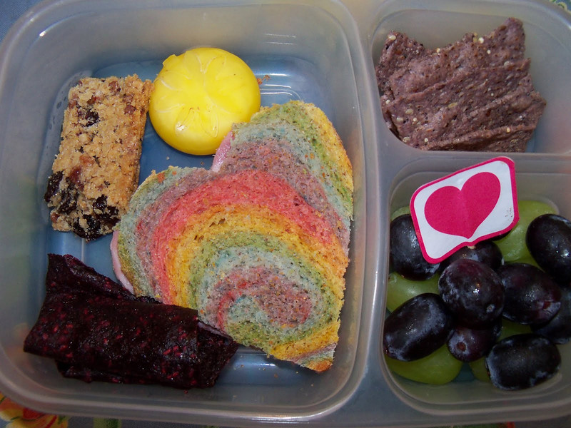 A colorful heart ham sandwich, a babybell with a sun cut into the wax, homemade berry fruit roll up, a chewy granola bar, black and green grapes, and some blue corn Food Should Taste Good chips. You can find out how to make this colorful bread on Lunches Fit For a Kid:  http://bit.ly/dm3Z8R